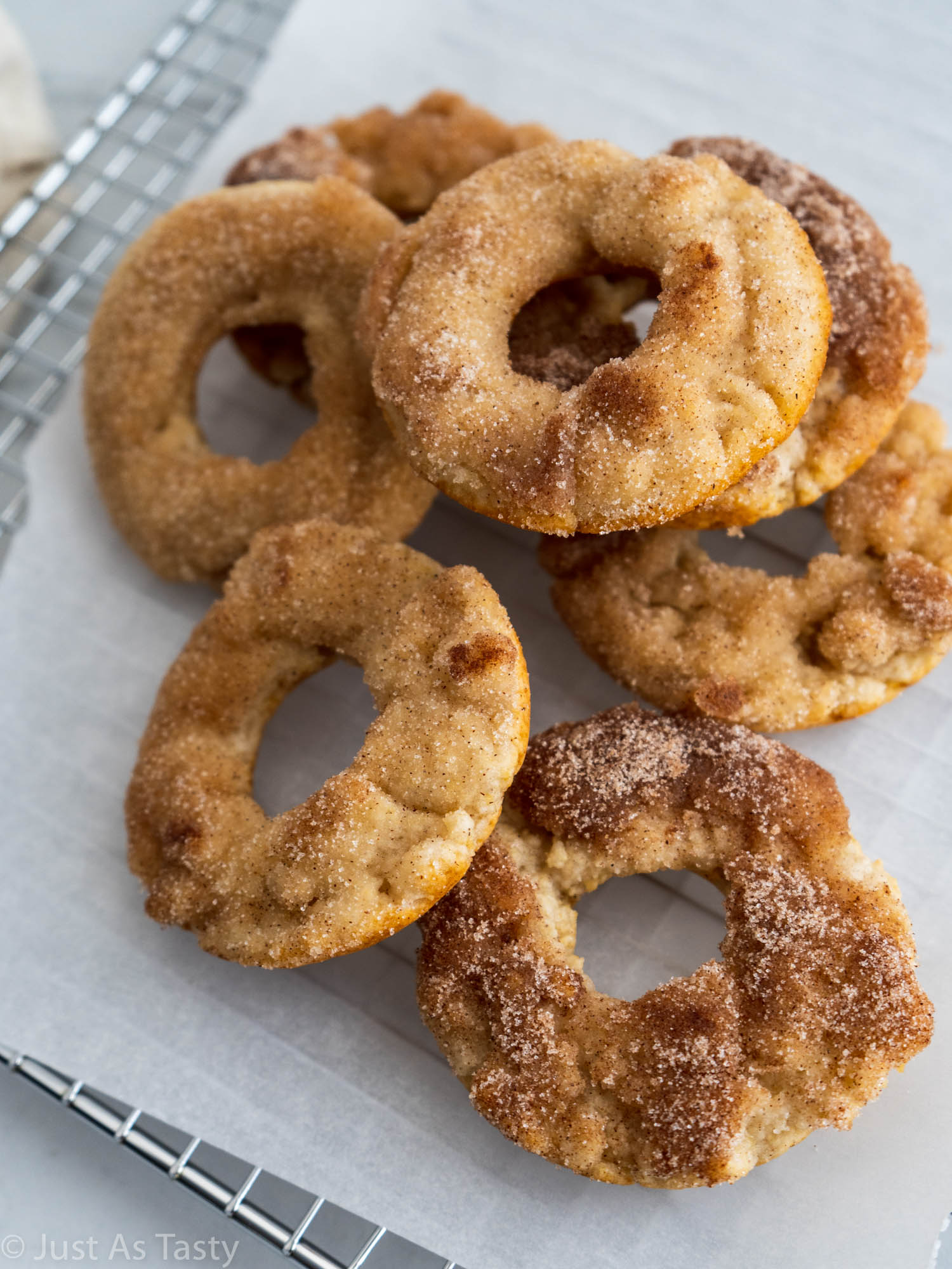 Baked donuts piled onto white parchment paper.