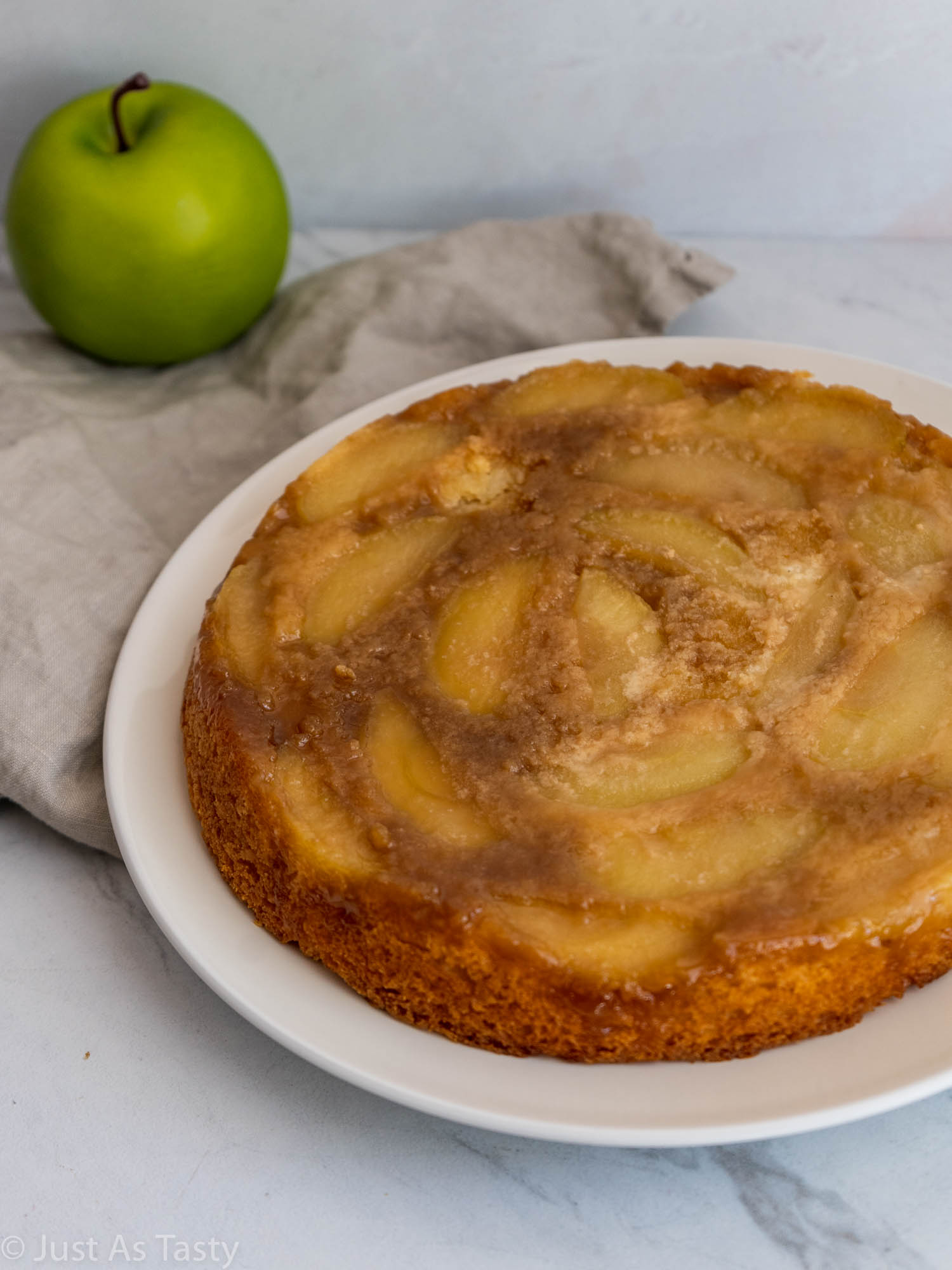 Gluten free single-layer apple cake on a white plate.
