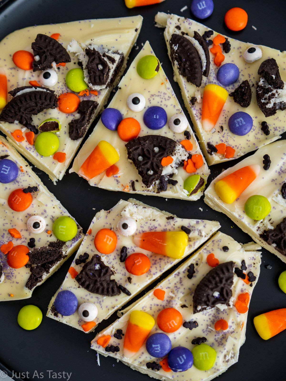 Pieces of white chocolate Halloween bark topped with candy on a black plate.