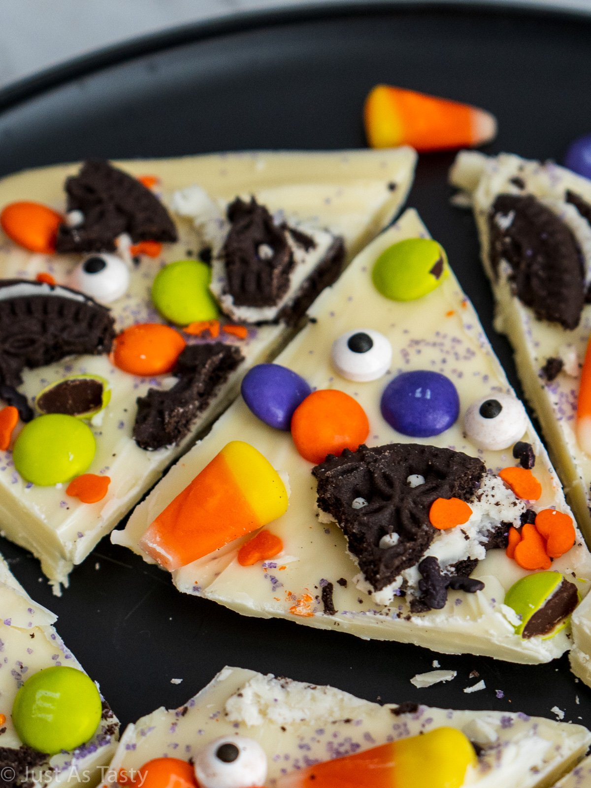 Close-up of a piece of white chocolate bark topped with Halloween candy and sprinkles.