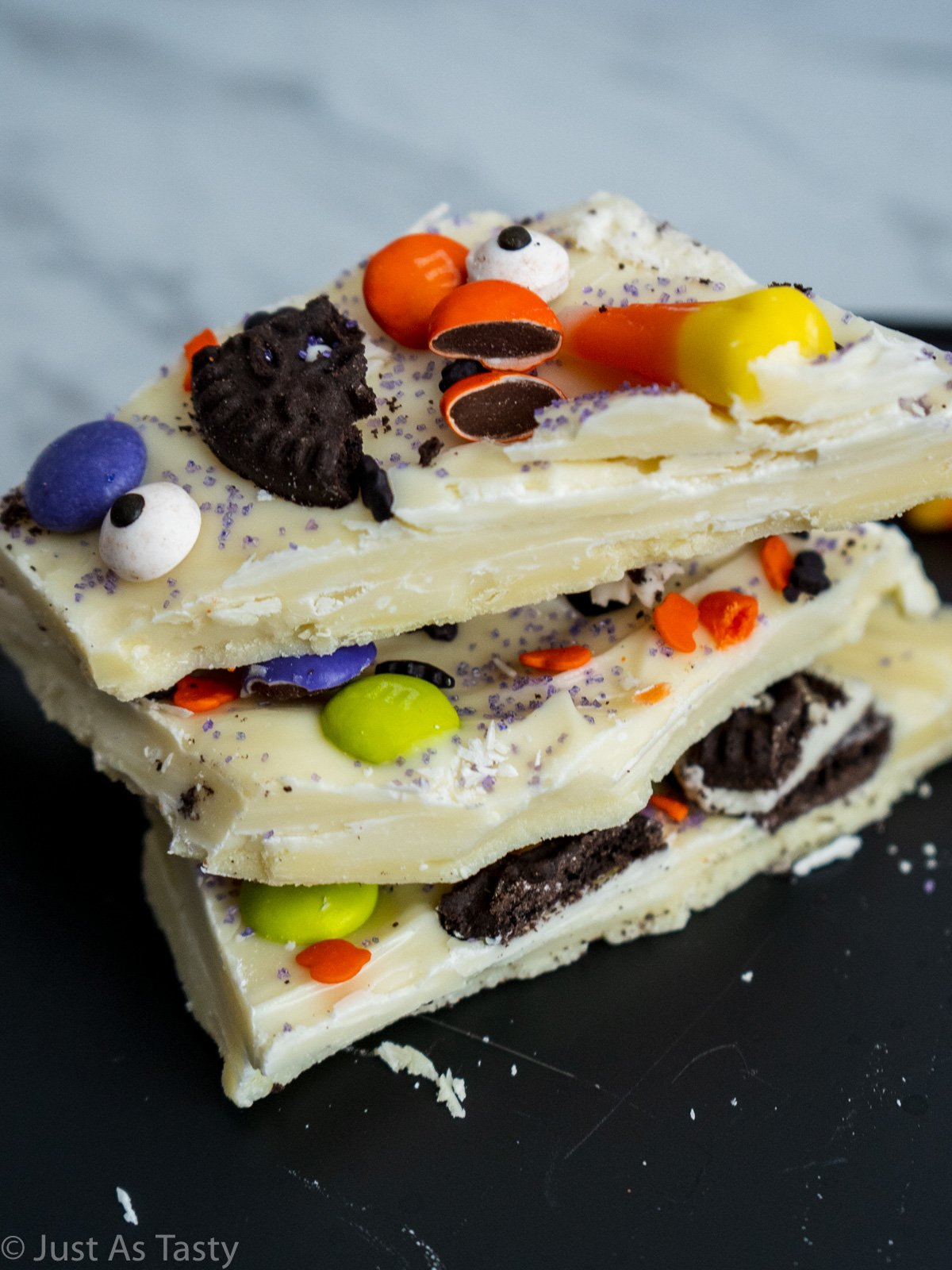 Stack of three pieces of Halloween chocolate bark topped with candy and sprinkles.