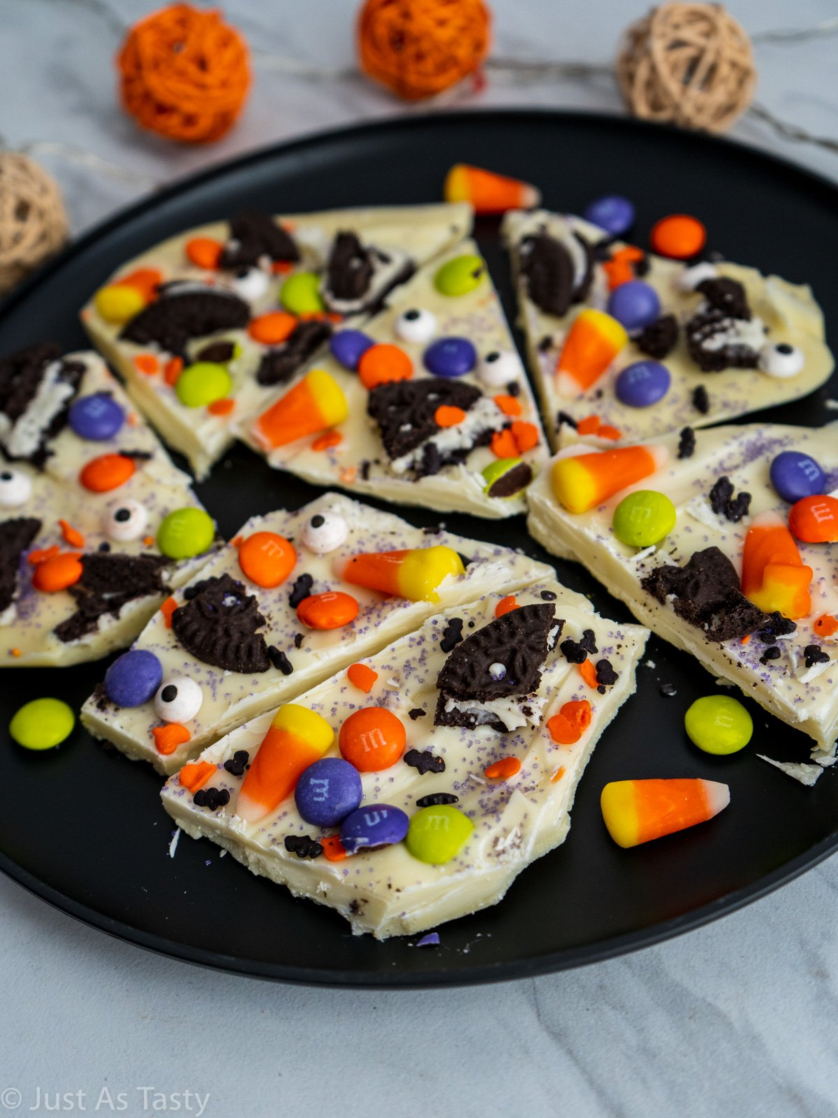 White chocolate bark topped with candy corn, Halloween sprinkles, and Oreo pieces on a black plate.