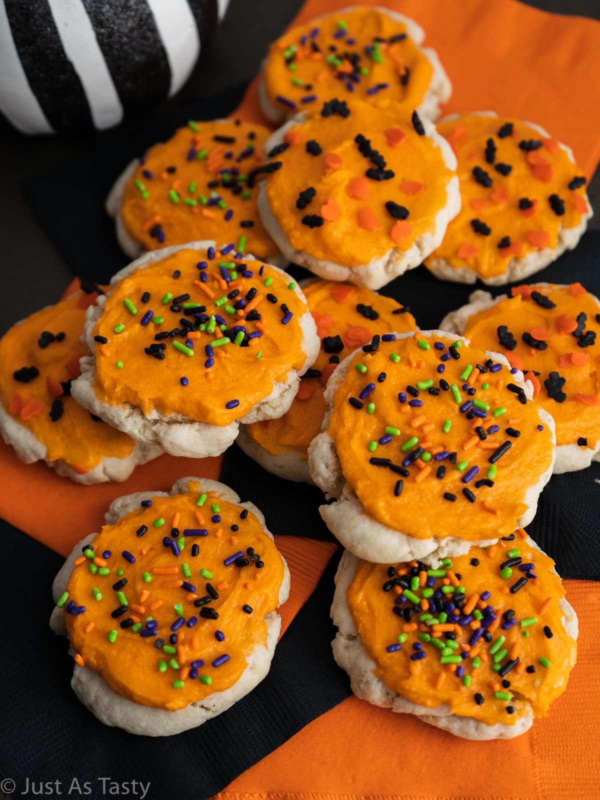 Lofthouse frosted sugar cookies topped with orange frosting and Halloween sprinkles.