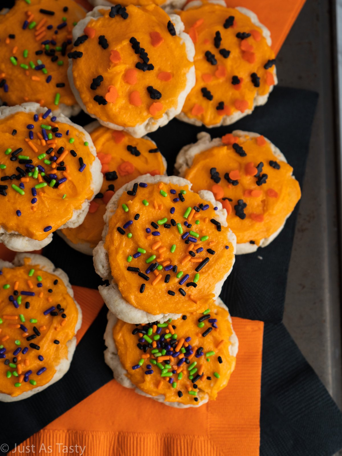 Round sugar cookies topped with orange buttercream frosting and Halloween sprinkles.