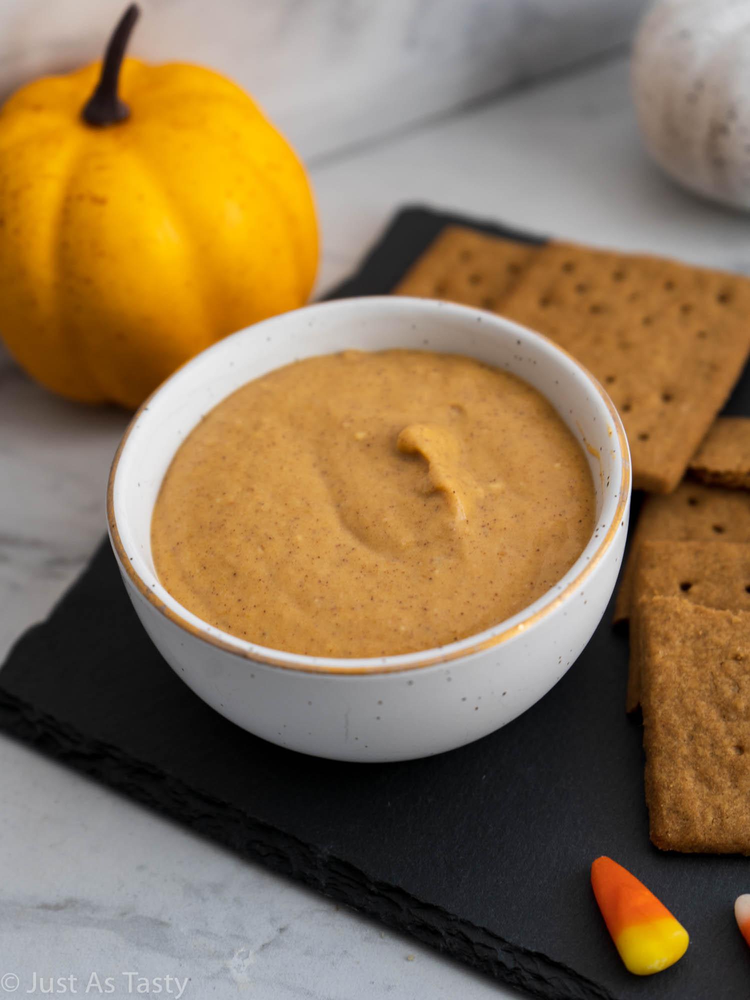 Pumpkin cream cheese dip in a white bowl.